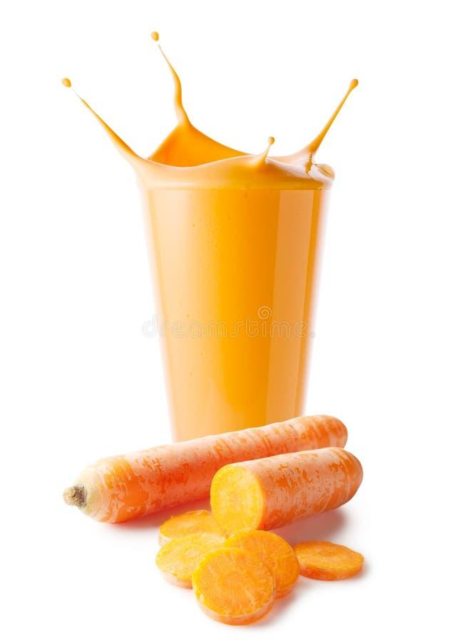 Chapoteo en el vidrio de smoothie o de yogur de la zanahoria con las zanahorias imagen de archivo libre de regalías