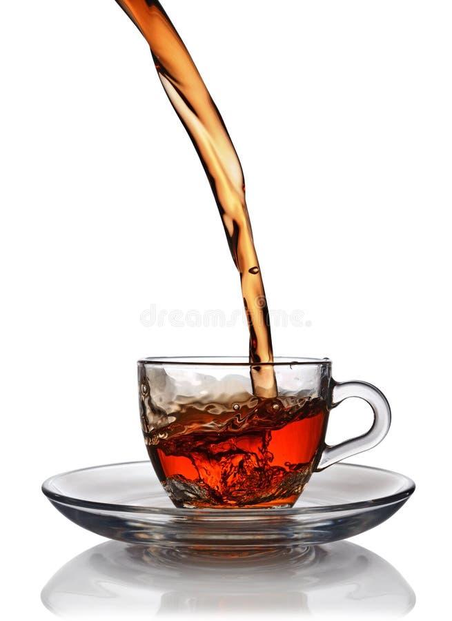 Chapoteo en la taza de cristal de té negro fotos de archivo libres de regalías
