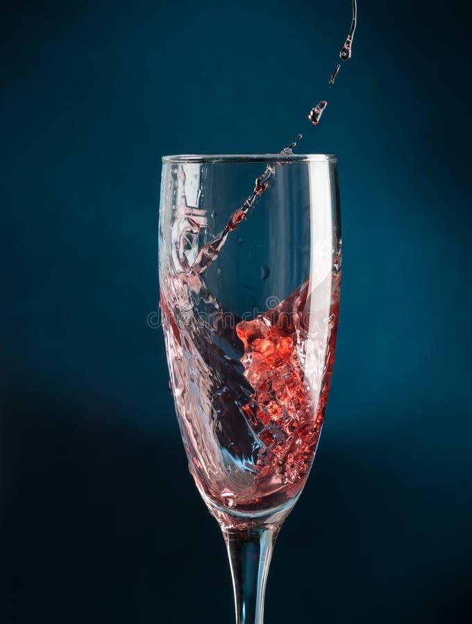 Chapoteo en un vidrio del champán del vino tinto que cae en un fondo azul marino imagenes de archivo