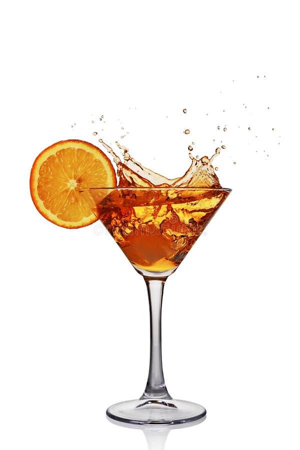 Chapoteo en vidrio de la bebida alcohólica transparente del cóctel con la naranja y el hielo de la rebanada fotografía de archivo libre de regalías