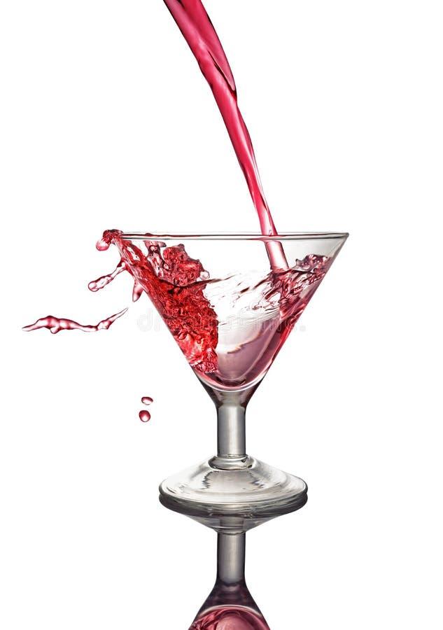 Chapoteo en vidrio de una bebida alcohólica rosada del cóctel imágenes de archivo libres de regalías