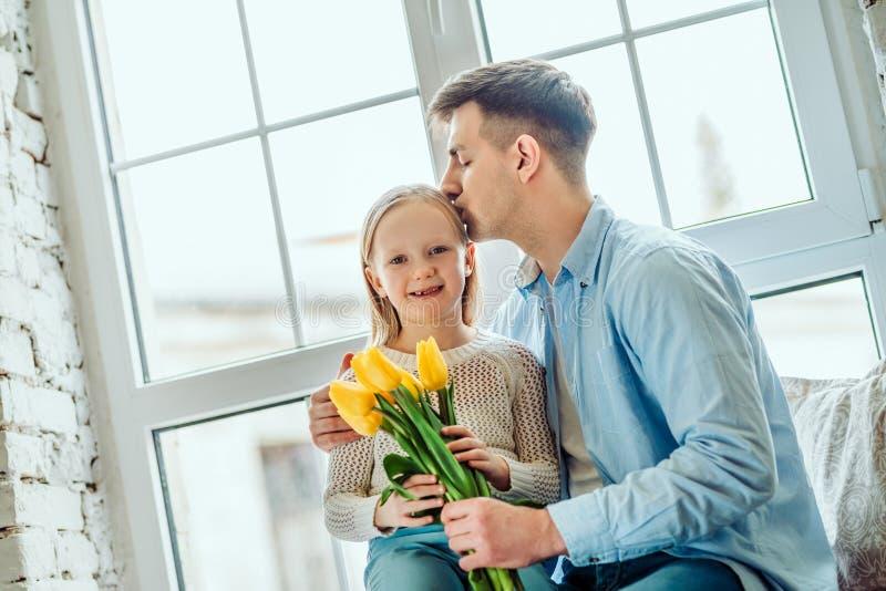 Chaque moment avec elle est précieux Fille et père s'asseyant ensemble sur le rebord de fenêtre à la maison Peu bouquet de partic image libre de droits