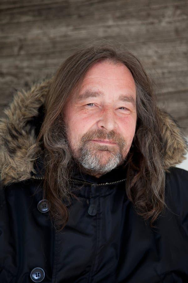 Chaqueta con capucha que lleva sonriente del hombre adulto largo del pelo foto de archivo