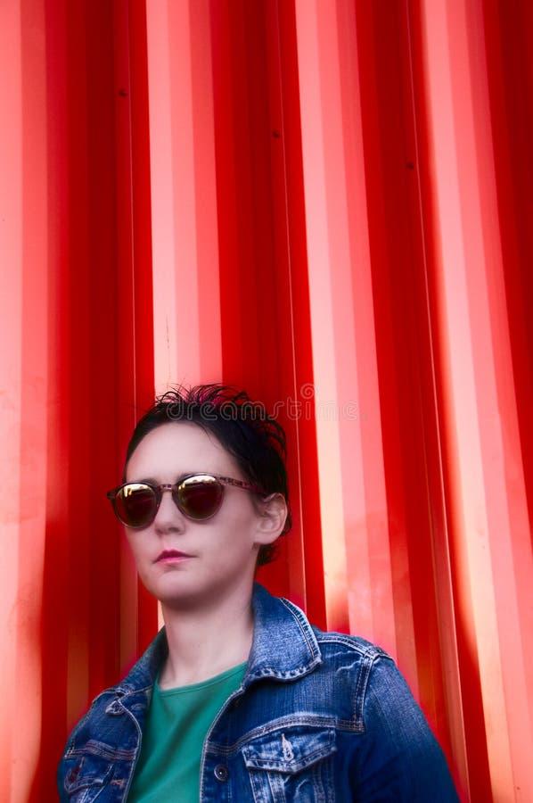 Chaqueta de la mezclilla de la mujer que lleva y fondo anaranjado imagen de archivo libre de regalías