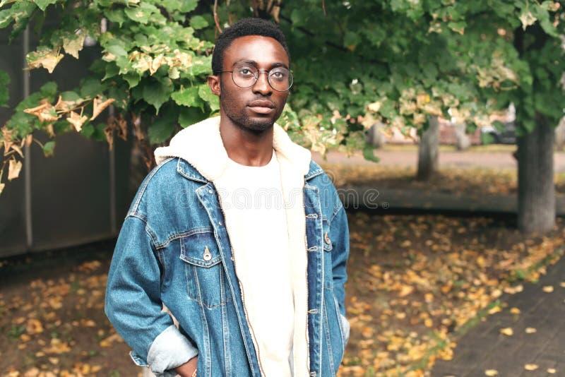 Chaqueta de los vaqueros del hombre africano del retrato de la moda que lleva, lentes en parque del otoño foto de archivo