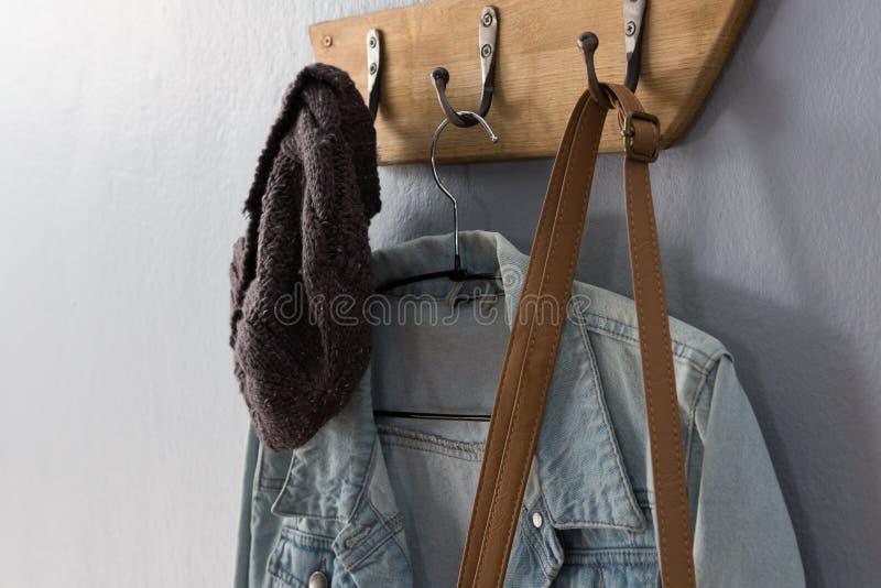 Chaqueta del dril de algodón, sombrero y ejecución del bolso en el gancho foto de archivo