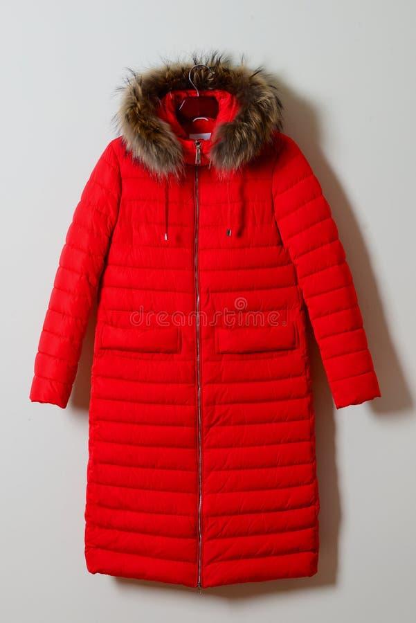 Chaqueta del invierno con una capilla en la piel con una cremallera outerwear Una chaqueta femenina larga en la suspensión, aisla fotos de archivo