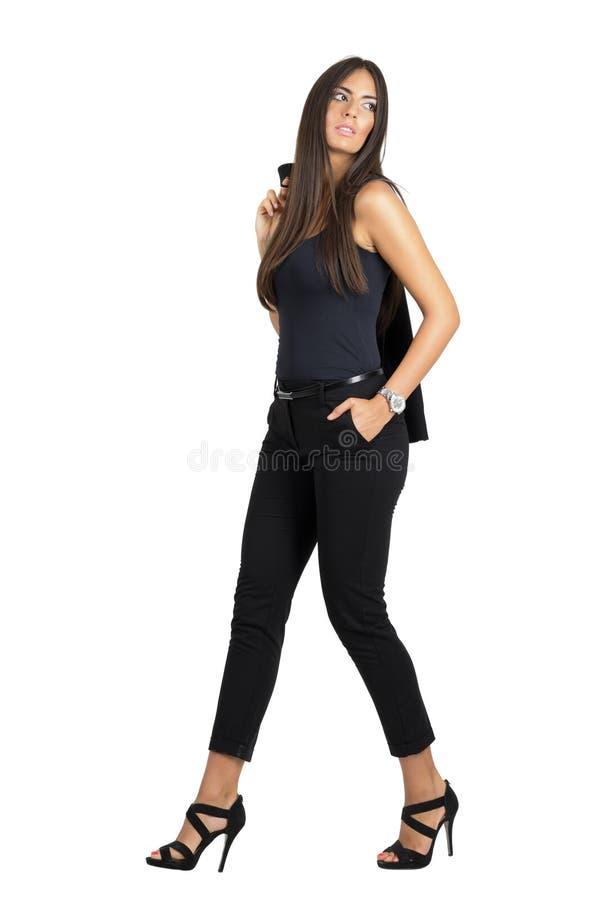 Chaqueta que lleva de la mujer latina atractiva magnífica del hombro que mira lejos imagen de archivo libre de regalías