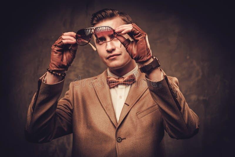 Chaqueta y corbata de lazo que llevan vestidas sostenido del hombre imagen de archivo