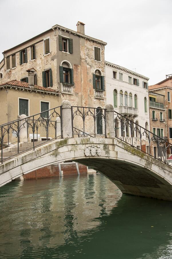 Characteristic bridge over a canal in Venice, Italy. Marble construction. Old houses. Venice Italia royalty free stock photography