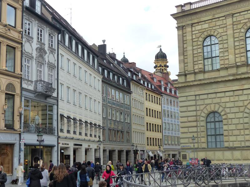 Characteristic crowded street of Munich in Germany. Cloudy sky. Colored ancient buildings. Street with a lot of people. Decorated bell  towers in distance stock photos