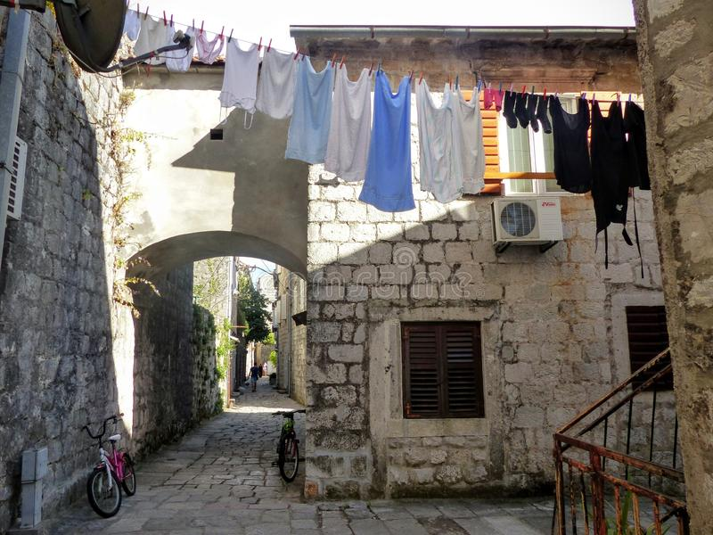 Characteristic road in the shade of Perast in Montenegro with some suspended laundry. royalty free stock photos