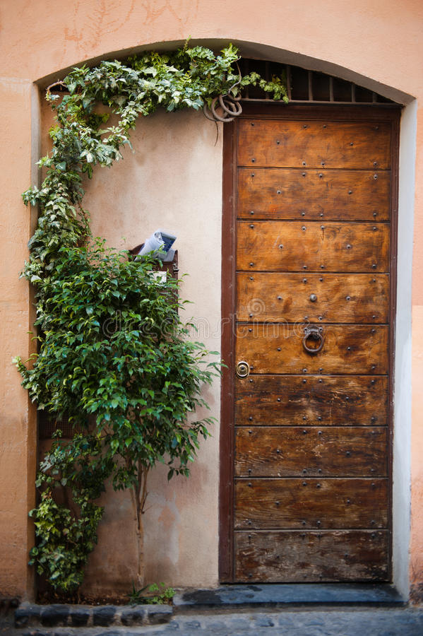 Characteristic wooden front door with flowerpot in Rome, Italy stock photography