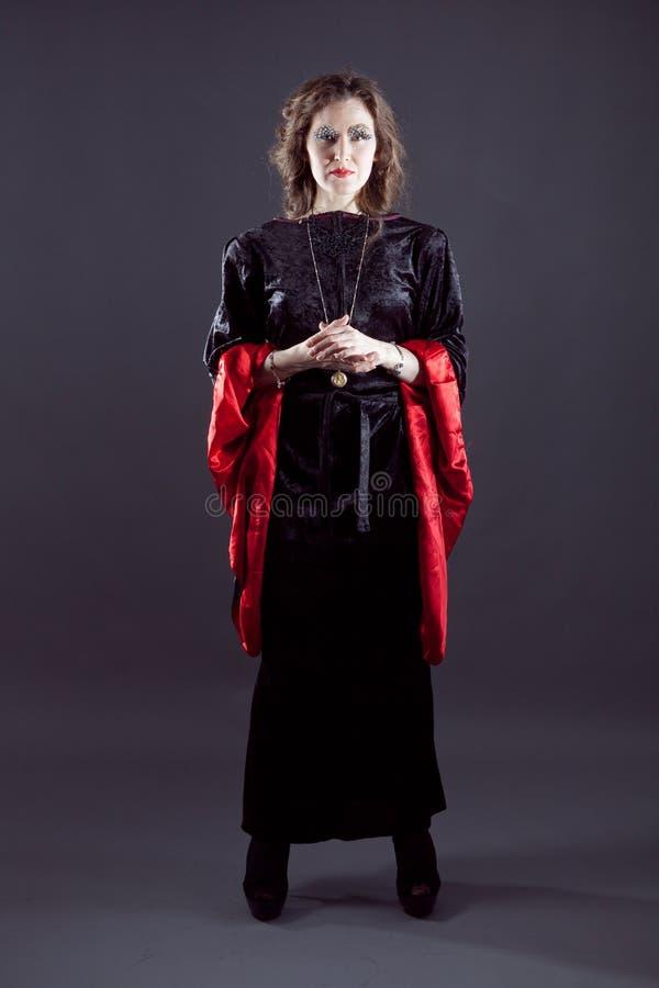 Junge Frauen im schwarzen langen Kleid lizenzfreie stockbilder