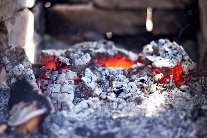 Charbons d'un rouge ardent brûlants sur le fond de la brique photos libres de droits