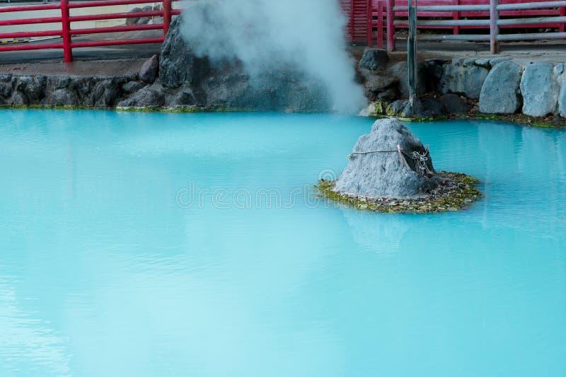 Charca azul de las aguas termales y del vapor fuera de la piedra imagenes de archivo