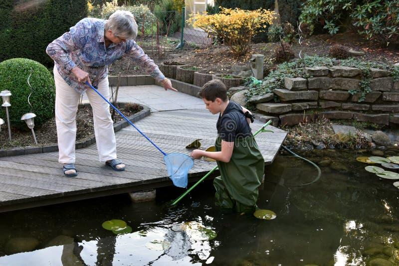 Charca del jardín de la limpieza del muchacho y de la abuela fotos de archivo libres de regalías