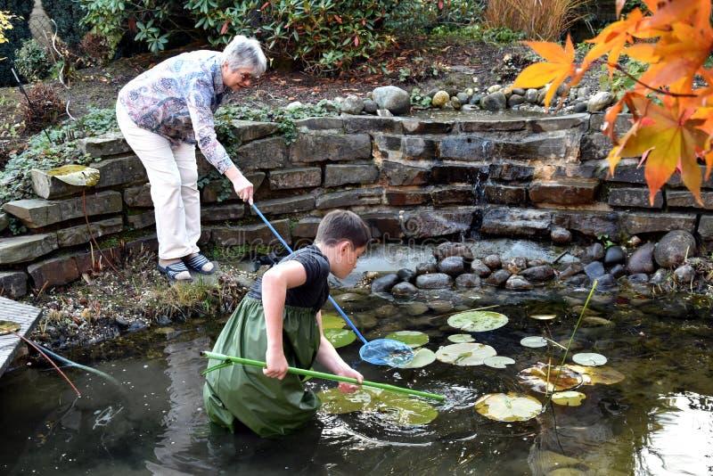 Charca del jardín de la limpieza del muchacho y de la abuela imagen de archivo libre de regalías