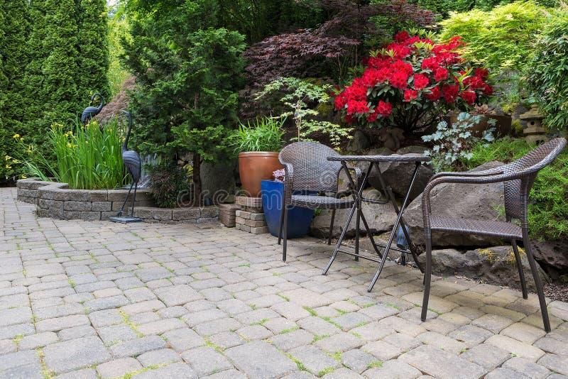 Charca del patio trasero del jardín que ajardina con primavera de los muebles de los bistros fotografía de archivo