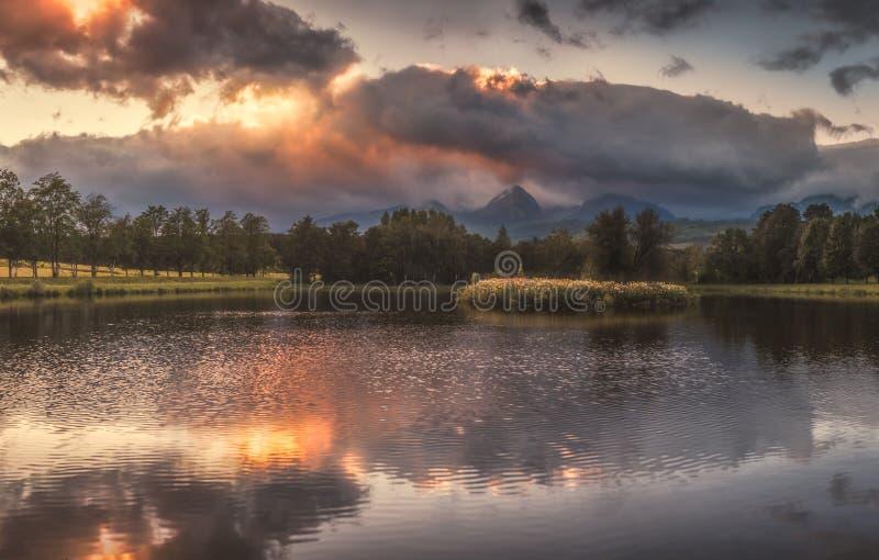 Charca encendida por la luz de oro en la puesta del sol con las montañas en fondo imagen de archivo