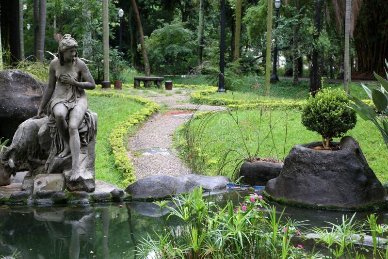 Charca hermosa con la escultura en parque público imagenes de archivo