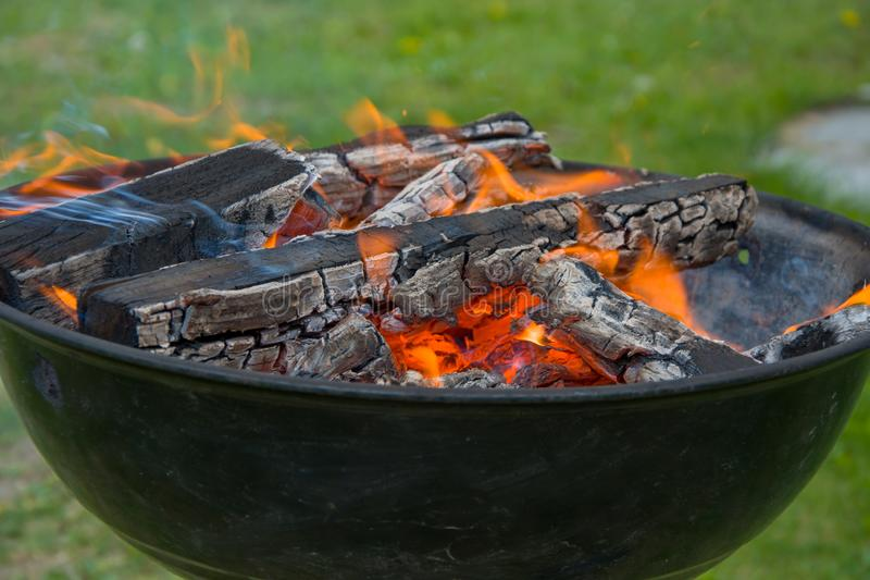 Charcoal barbecue grill, mobile brazier, burning wood stock images