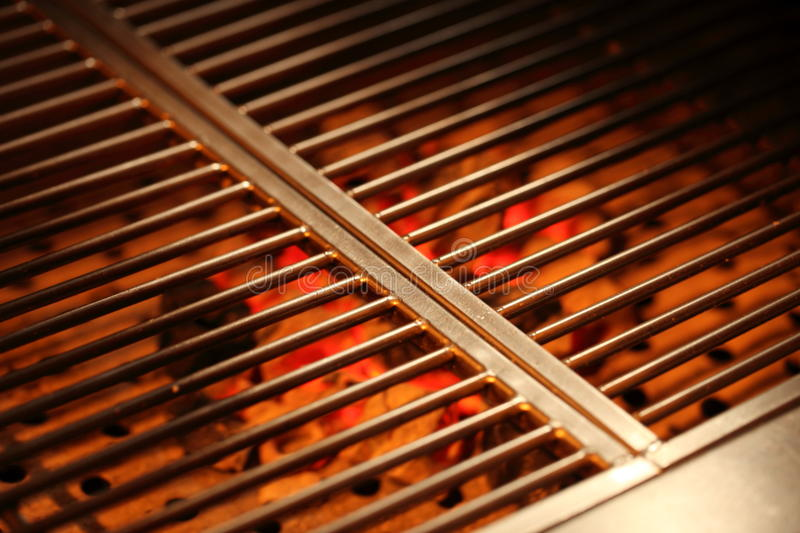 Charcoal Grill. Burning charcoal under an iron grill royalty free stock image