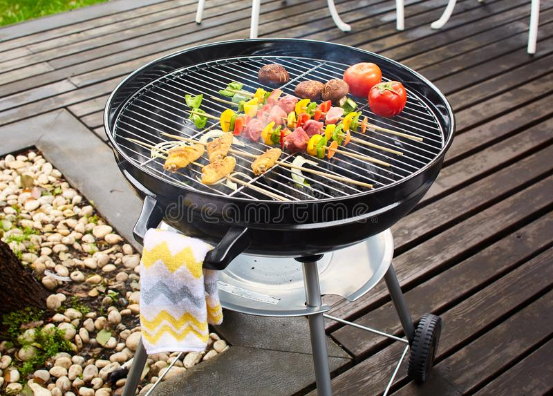 Charcoal grill on terrace. A charcoal grill with vegetables and barbecue on a terrace royalty free stock photos