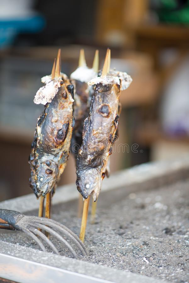 Charcoal grilled Ayu fish with salt. NIKKO, JAPAN - NOVEMBER 08, 2018:Charcoal grilled Ayu fish with salt. Traditional Japanese street food at Kegon waterfall in stock photo