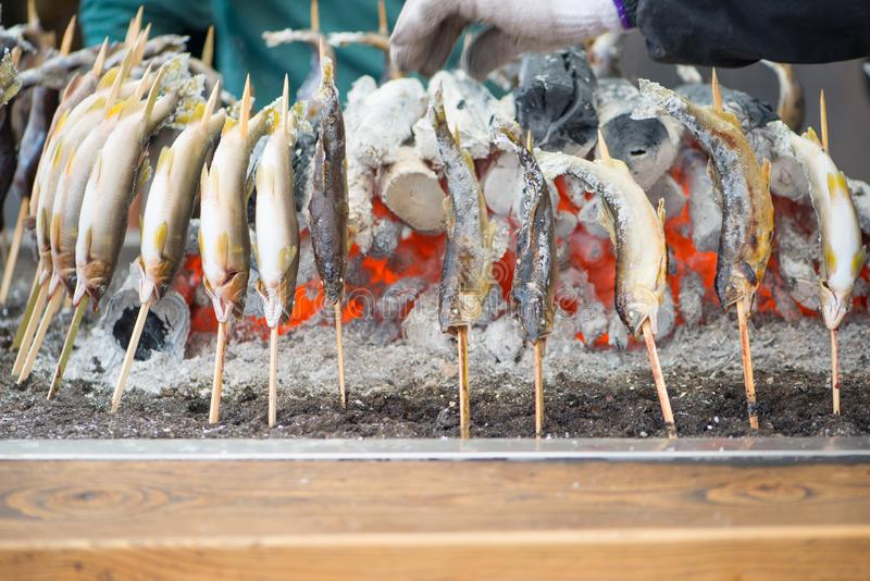 Charcoal grilled Ayu fish with salt. NIKKO, JAPAN - NOVEMBER 08, 2018:Charcoal grilled Ayu fish with salt. Traditional Japanese street food at Kegon waterfall in royalty free stock photography