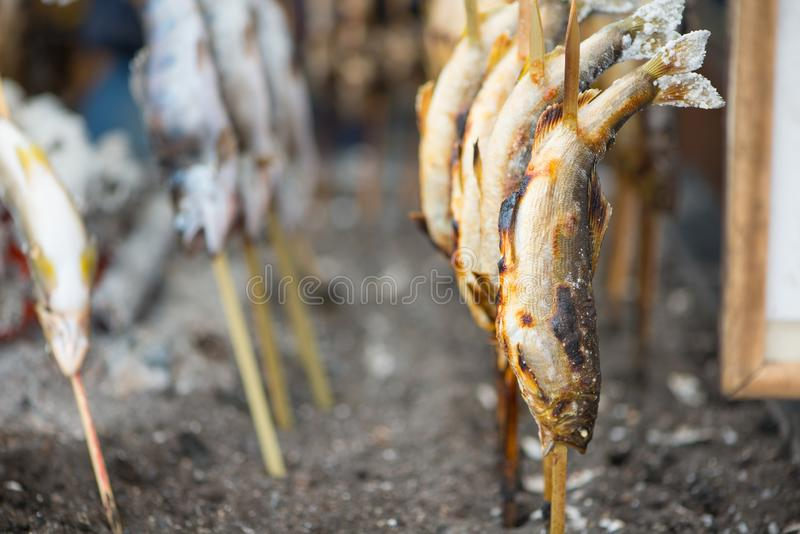 Charcoal grilled Ayu fish with salt. NIKKO, JAPAN - NOVEMBER 08, 2018:Charcoal grilled Ayu fish with salt. Traditional Japanese street food at Kegon waterfall in stock photos