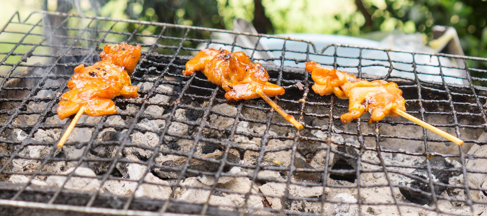 Charcoal grilled chicken. On barbecued mesh and hot stove stock photo