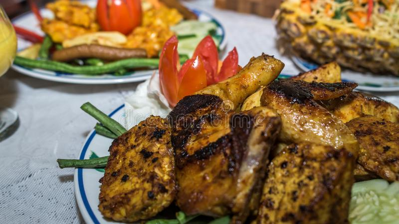 Charcoal grilled chicken with curry sauce. Served with other dishes royalty free stock image