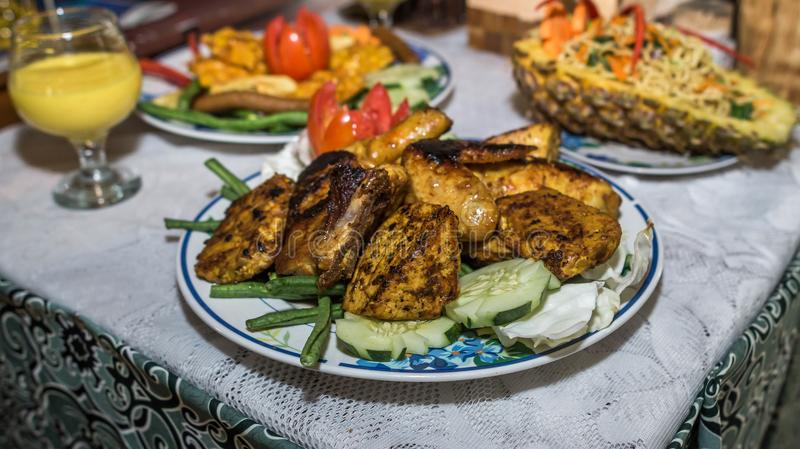 Charcoal grilled chicken with curry sauce. Served with other dishes royalty free stock photos