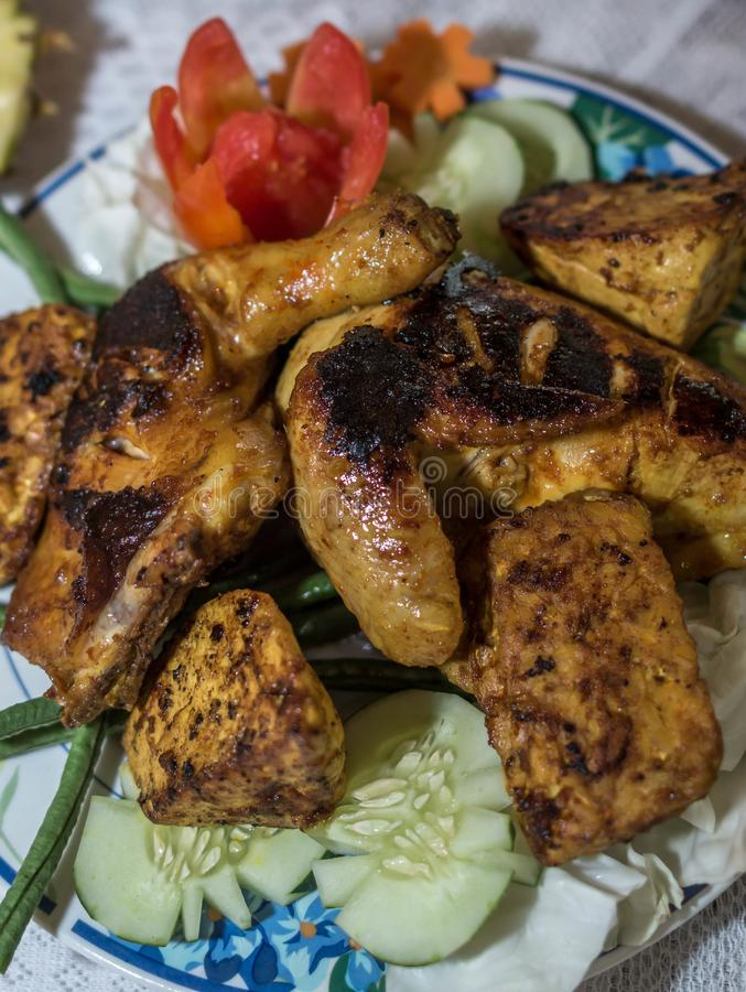 Charcoal grilled chicken with soy sauce, Asia culinary. Charcoal grilled chicken with soy sauce garnished with cucumber and tomato, Asia culinary stock images