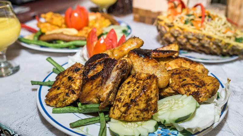 Charcoal grilled chicken with curry sauce. Charcoal grilled chicken with soy sauce garnished with cucumber and tomato, Asia culinary stock image