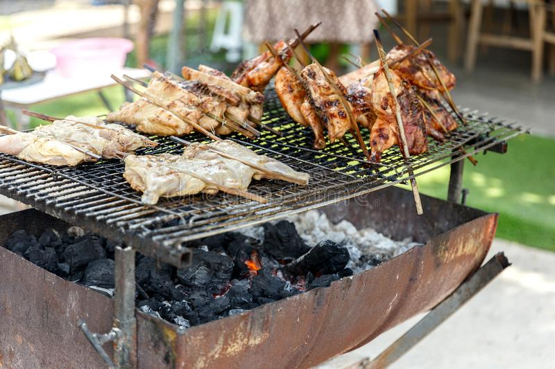 Thai Street Food : Charcoal Grilled roast Chickens on the stove half cut oil tank. Charcoal Grilled roast Chickens on the stove half cut oil tank stock photography