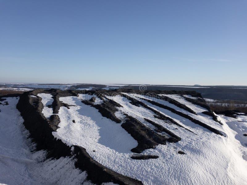 Charcoal mountain under the snow. Black charcoal mountain under the white snow. Sunny day, cold whether stock photos