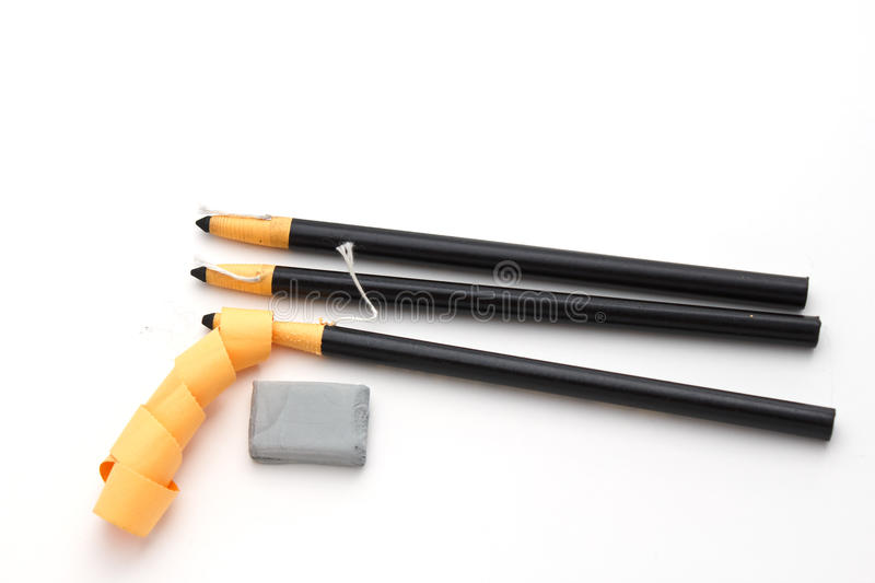 Charcoal pencils and eraser. Isolated on a white background with one pencil being peeled of its wrapper royalty free stock image