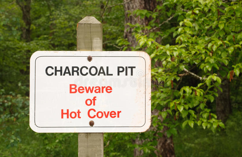 Charcoal Pit. And beware of hot cover sign in park setting stock image