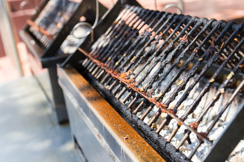Charcoal stove and gridiron for barbecue grilling. The charcoal stove and gridiron for barbecue grilling sausage or meat product royalty free stock photo