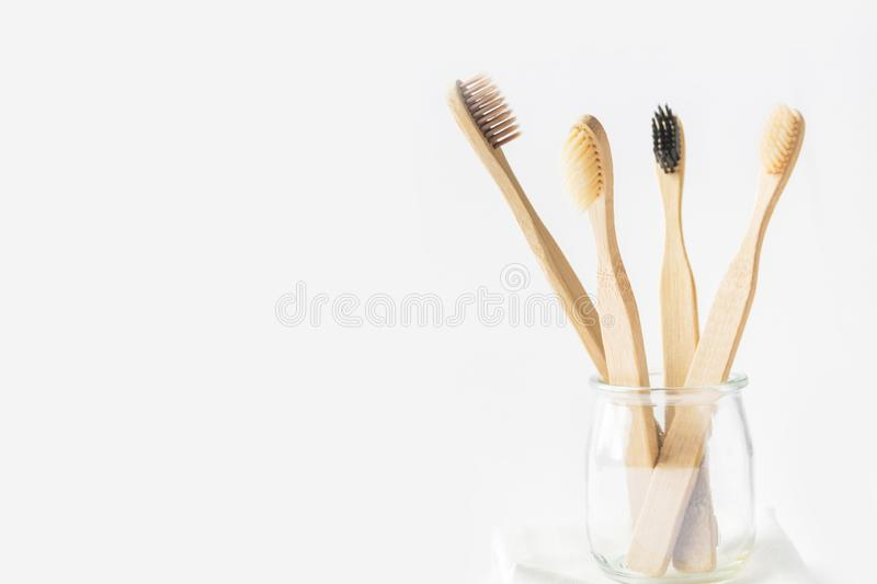Charcoal wooden bamboo toothbrushes in glass cup on white background. Zero waste plastic free eco friendly reusable materials royalty free stock photo
