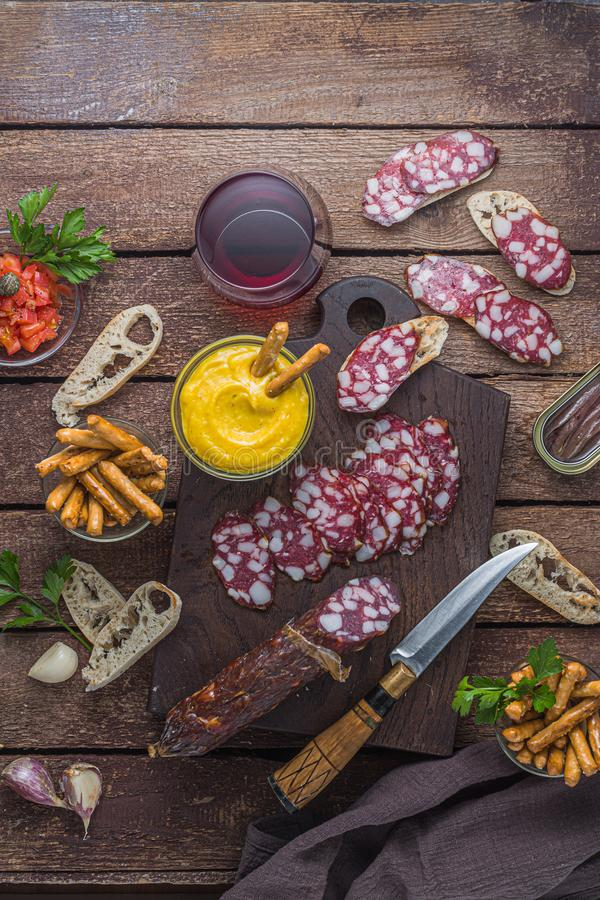 Charcuterie board with salami and alioli dip, red wine.  royalty free stock photography