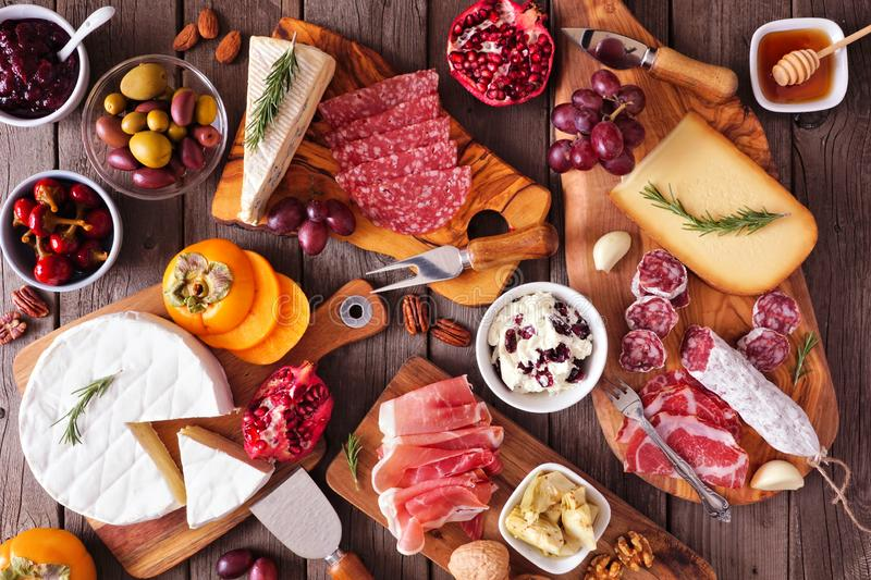Charcuterie boards of assorted cheeses, meats and appetizers, above view table scene on rustic wood stock photography