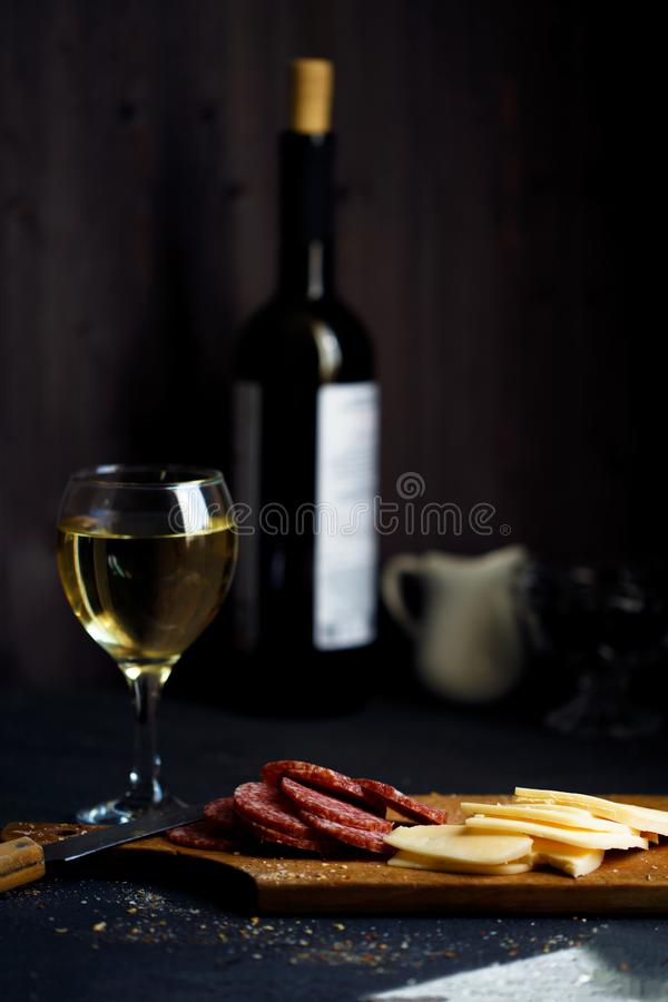 Charcuterie, cheese, salami and a glass of wine on a dark table. Close up royalty free stock photography