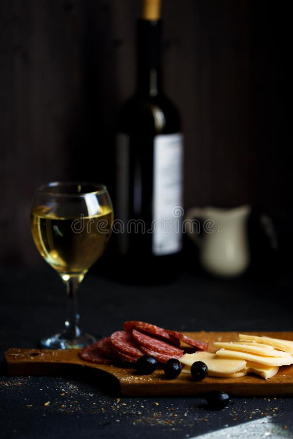 Charcuterie, cheese, salami, olives and a glass of wine on a dark table. Close up stock photo