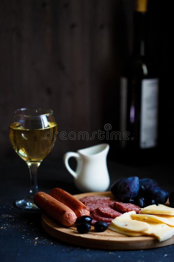 Charcuterie, grilled sausages, cheese, salami, plum olives and a glass of wine on a dark table. Copy space stock photos