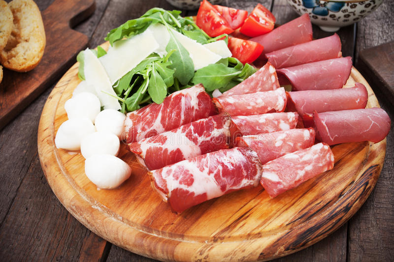 Charcutertie board with italian cured meat. Charcuterie board with italian cured meat, cheese and rocket salad royalty free stock photo