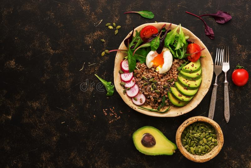 Κουάκερ φαγόπυρου με το βρασμένα αυγό, το αβοκάντο, το ραδίκι, chard τα φύλλα, το arugula, την ντομάτα, τις κολοκύθες σπόρων και  στοκ φωτογραφία με δικαίωμα ελεύθερης χρήσης