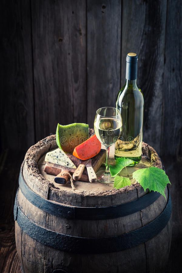 Chardonnay wine and mix of cheese on oak barrel. On wooden background stock image